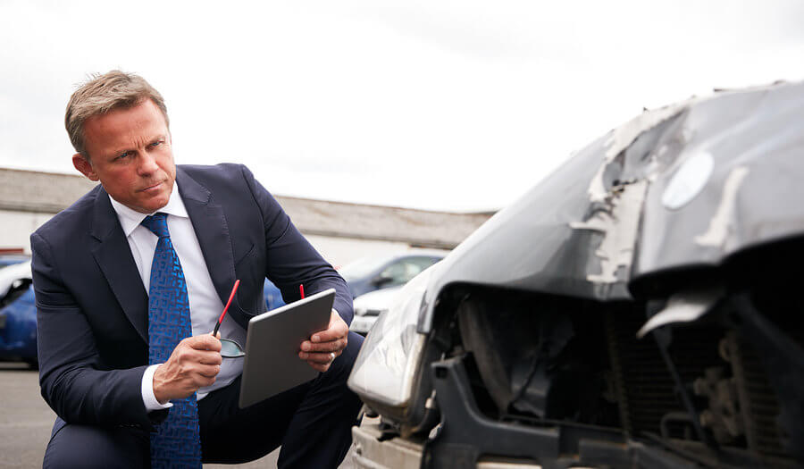 insurance claims adjuster checking a damaged car