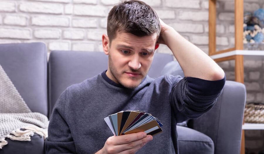 young man holding many cards