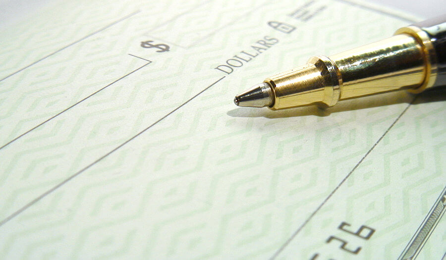 a paper check with a pen