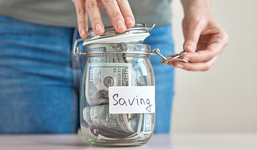 man closing the top of a savings jar