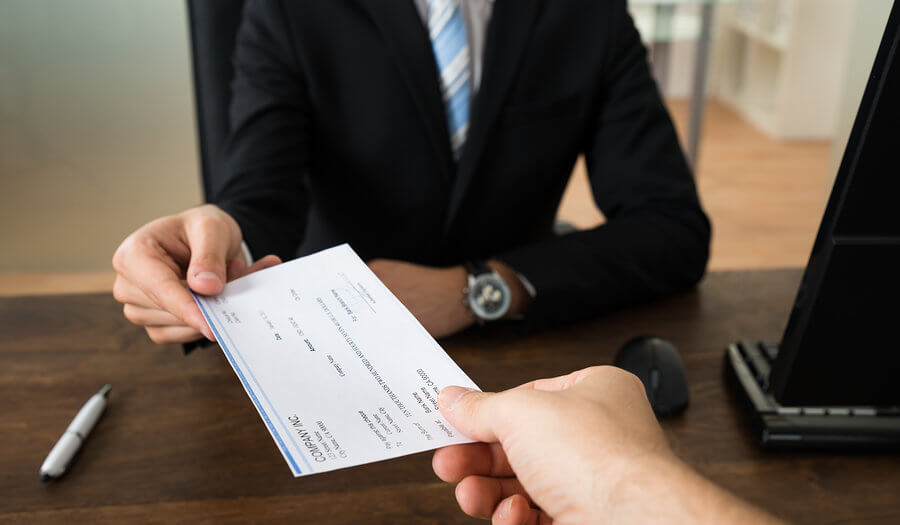 man giving a check to a bank teller